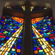 A stained glass window depicting a cross is shown from the inside.