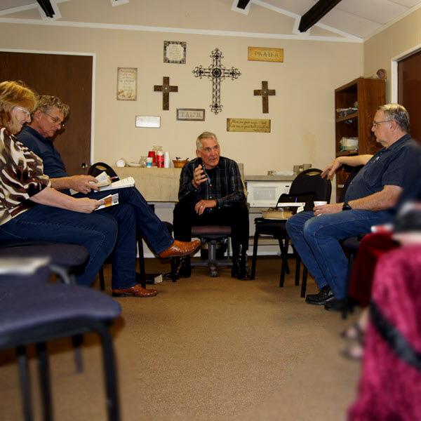 A group of adults listen to a teacher.