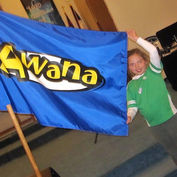 A girl displays a colorful Awana flag.