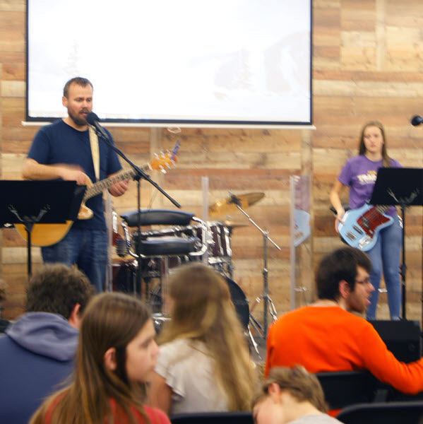 A student pastor leads a group of teens in worship.
