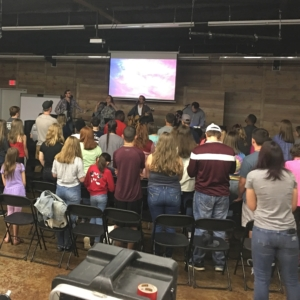 Group of teens is led in worship by a praise band.